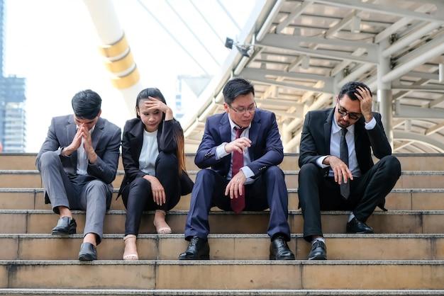Aziatische zakenlieden die somber wegens werkloosheid zitten. Premium Foto