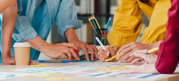 Aziatische zakenlieden en vrouwelijke ondernemers brainstormen over creatieve webdesign planningstoepassing en het ontwikkelen van sjabloonlay-out voor mobiele telefoonproject samen te werken in een klein kantoor. Gratis Foto