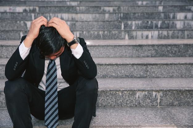 Aziatische zakenlieden met hoofdpijnen of migraine bij het stadhuis na het werk Premium Foto
