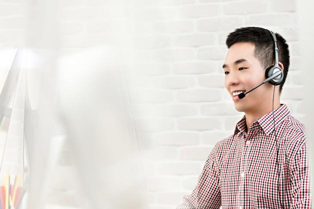 Aziatische zakenman die in call centre als agent van de telemarketerdienst werkt Premium Foto
