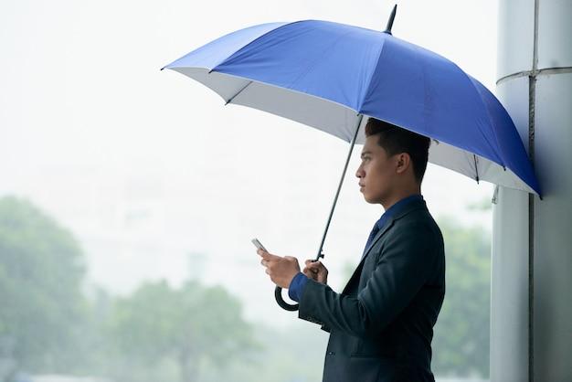 Aziatische zakenman die zich in straat met paraplu tijdens regen bevinden en smartphone gebruiken Gratis Foto