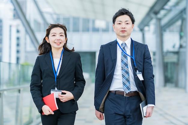 Aziatische zakenman en vrouw in kostuums die zij aan zij lopen Premium Foto