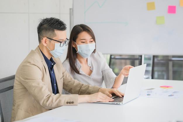 Aziatische zakenman en zakenvrouw draagt gezichtsmasker voor bescherming coronavirus bespreken zakelijk project Premium Foto