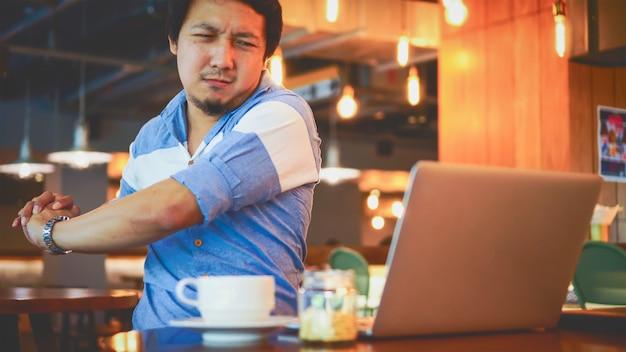Aziatische zakenman in casual pak werken met nekpijn, rugpijn of hoofdpijn Premium Foto