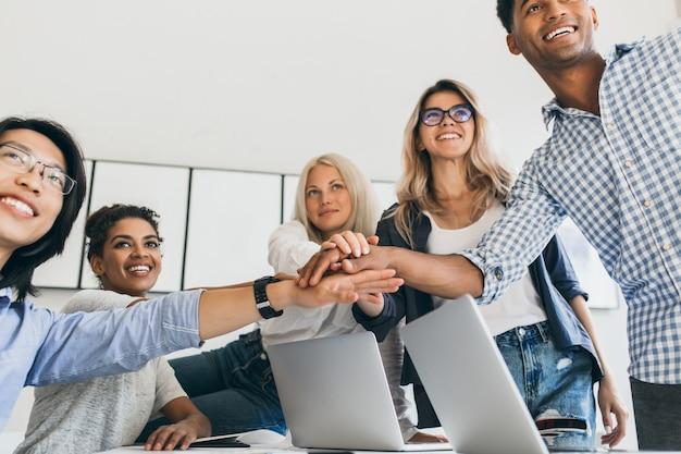 Aziatische zakenman in lederen polshorloge hand in hand met partners en glimlachen. indoor portret van team van kantoorpersoneel met plezier voor groot project. Gratis Foto