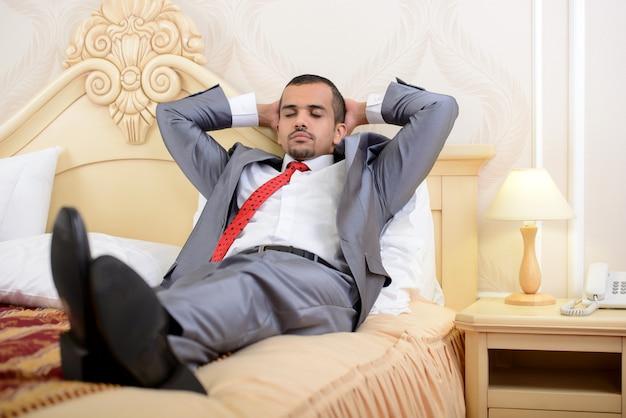Aziatische zakenman met koffer die op een bed ligt. Premium Foto