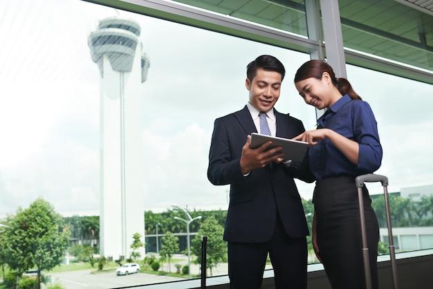 Aziatische zakenmensen die op luchthaven landen Gratis Foto
