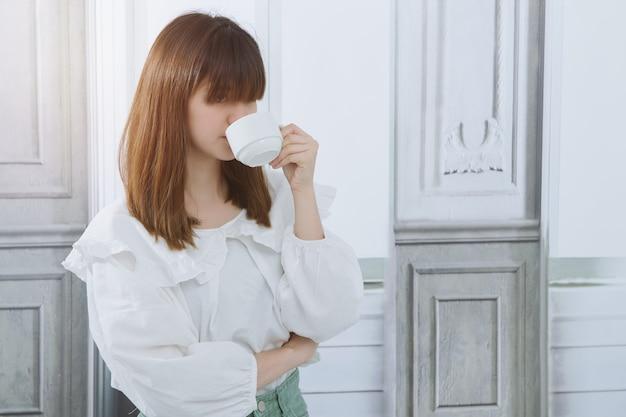 Aziatische zakenvrouw genoten van het moment van ontspanning en thuis het drinken van een kopje aroma koffie. vrouw met koffiekopje. Premium Foto