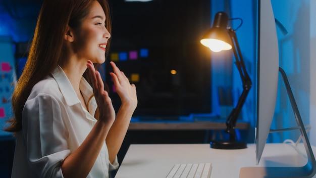 Aziatische zakenvrouw met behulp van computer praten met collega's over plan in videogesprek tijdens het werken vanuit huis in de woonkamer 's nachts. zelfisolatie, sociale afstand nemen, quarantaine voor coronaviruspreventie. Gratis Foto