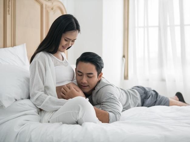Aziatische zwangere vrouw en echtgenoot die op het bed leggen terwijl samen het doorbrengen van tijd. Premium Foto
