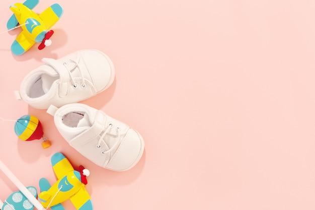 Baby concept. plat leggen accessoires met baby schoenen en houten speelgoed vliegtuig. Gratis Foto