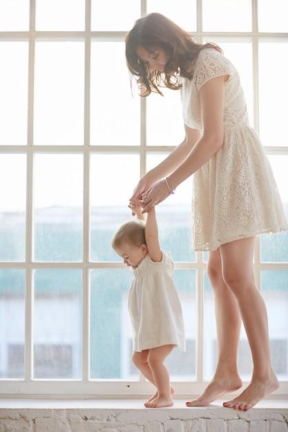 Baby die eerste stappen met de hulp van de moeder thuis zet. baby leunend wandelen met moeder Premium Foto