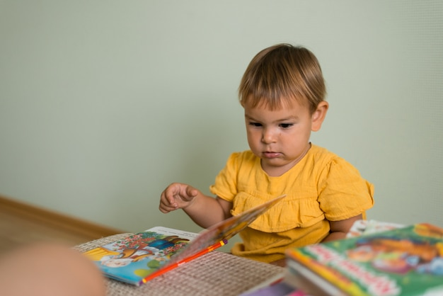 Baby die kleurrijke boeken in oekraïener thuis leest Premium Foto
