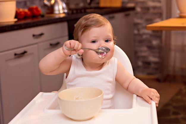 Baby die melkpap met een lepel eet Premium Foto