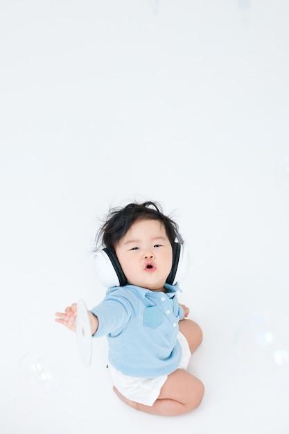 Baby geniet van het luisteren naar muziek op zijn koptelefoon. Premium Foto