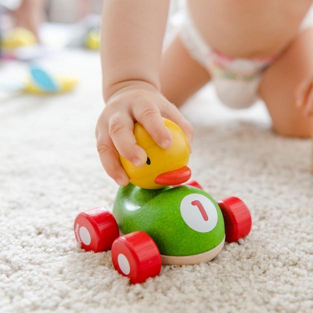 Baby het spelen met een houten auto Gratis Foto