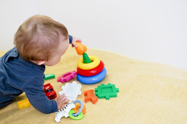 Baby het spelen met kleurrijk speelgoed thuis. vroege ontwikkeling voor kinderen. Premium Foto
