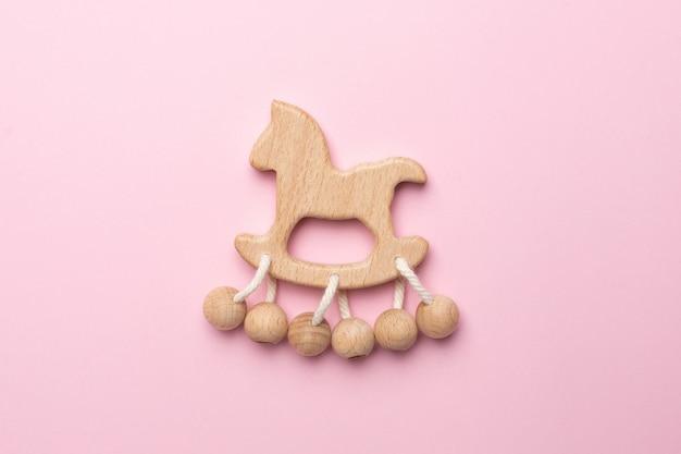 Baby houten rammelaar en speelgoed op roze Premium Foto
