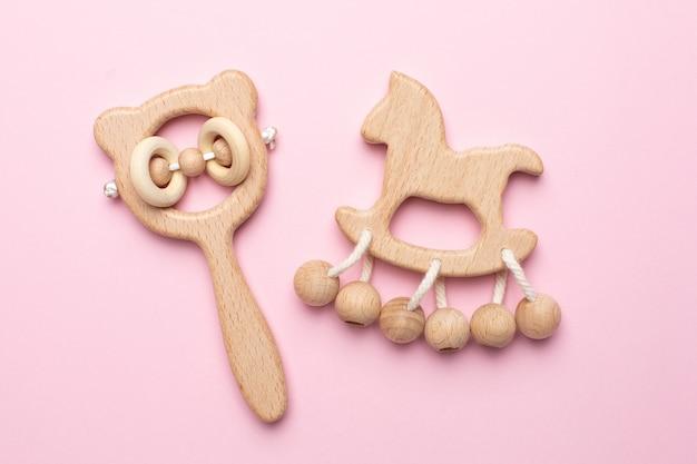 Baby houten rammelaars en speelgoed op roze Premium Foto