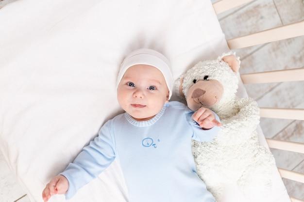Baby in de wieg, portret van een schattige baby 3 maanden in de wieg met een teddybeer speelgoed, kinderen en geboorte concept Premium Foto