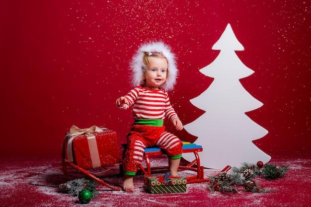 Baby in kerst pyjama's en kerstmuts vangt sneeuw zittend op een slee met geschenkdoos en grote witte kerstboom op rode achtergrond Premium Foto