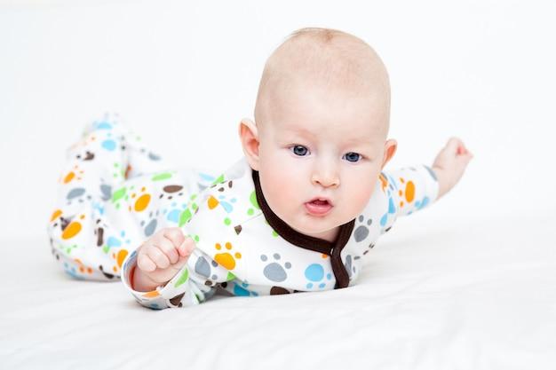 Baby in kleur uitglijden op het bed liggend op zijn buik Premium Foto