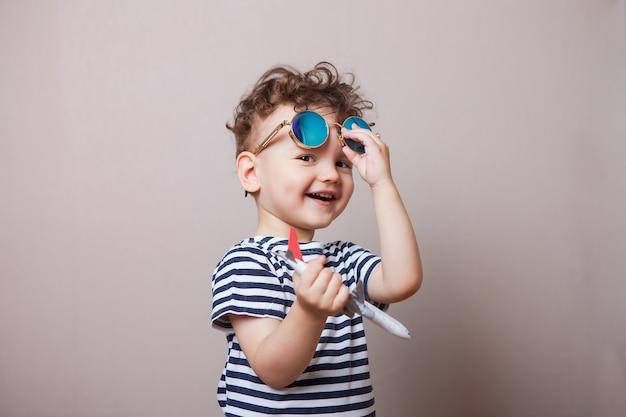 Baby, kind met een speelgoedvliegtuig in zijn handen en een zonnebril. toerist Premium Foto