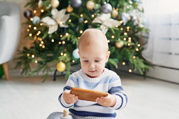 Baby kind portret met de kerstboom. kerst schattige peuter. familie vakantie concept. kinderen spelen kamer. kerst in de kinderkamer. kid met smartphone. Premium Foto