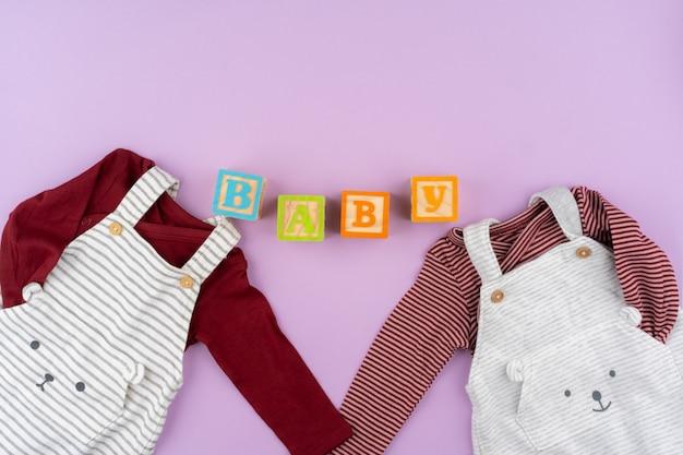 Baby meisje kleding op lila pastel achtergrond Premium Foto