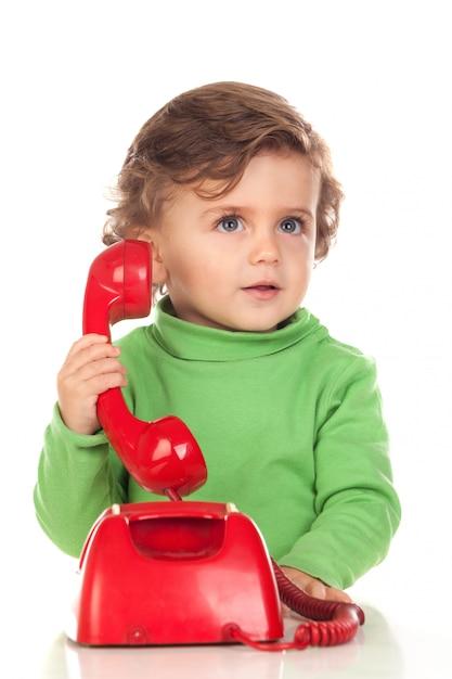 Baby met één jaar oud die met een rode telefoon speelt Premium Foto