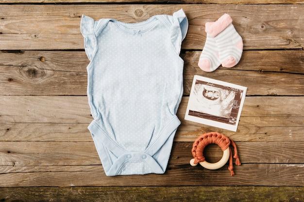 Baby onesie met paar sokken; echografie foto en speelgoed op houten tafel Gratis Foto