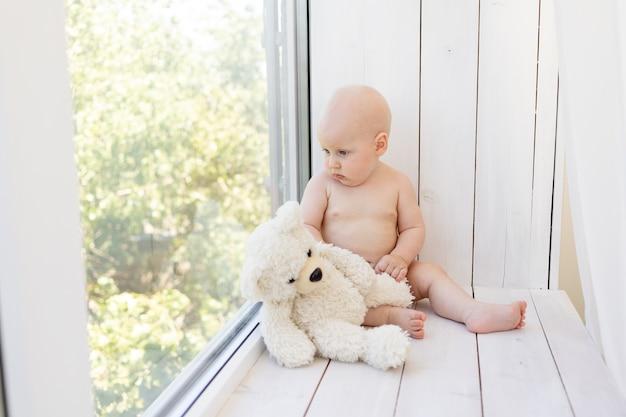 Baby op het raam met een teddybeer in luiers thuis Premium Foto