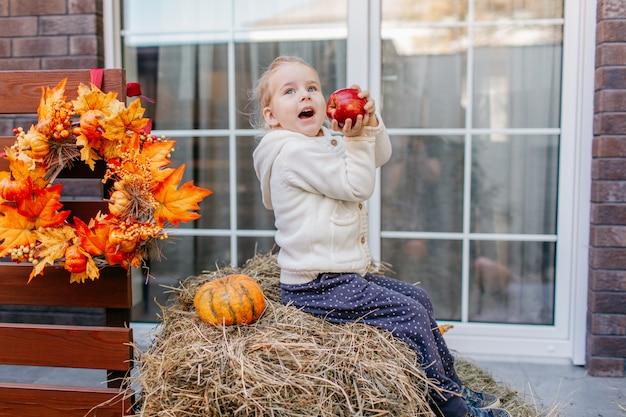 Baby peuter in witte gebreide jas zittend op de hooiberg met pompoenen op veranda en spelen met appel. Premium Foto