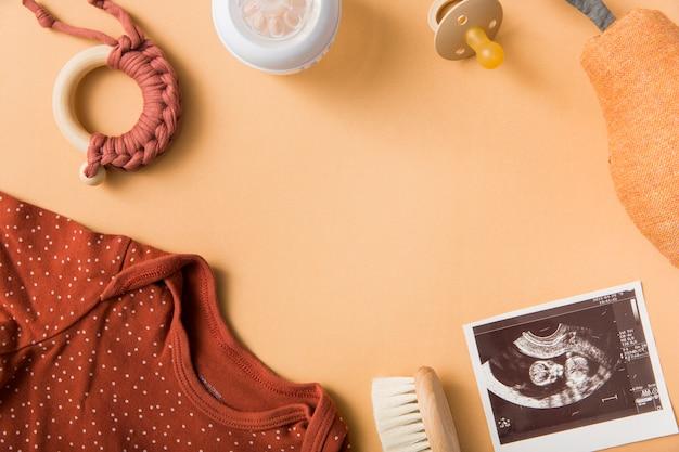 Baby's kleding; borstel; speelgoed; fopspeen; gevulde peer en echografie foto op een oranje achtergrond Gratis Foto
