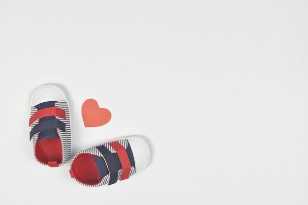 Baby schoenen met rood hart vorm op wit. kopie ruimte. Premium Foto