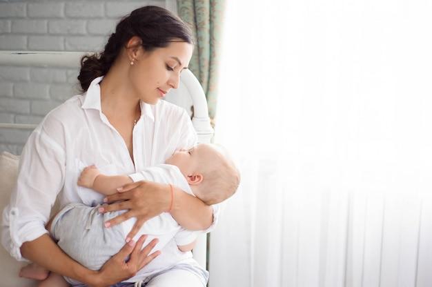 Baby slaapt op de borst van de moeder. jonge moeder knuffelende baby Premium Foto
