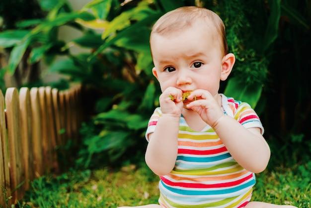 Baby verslindt een bloem die zichzelf uit de tuin geplukt heeft om de smaak te proeven. Premium Foto