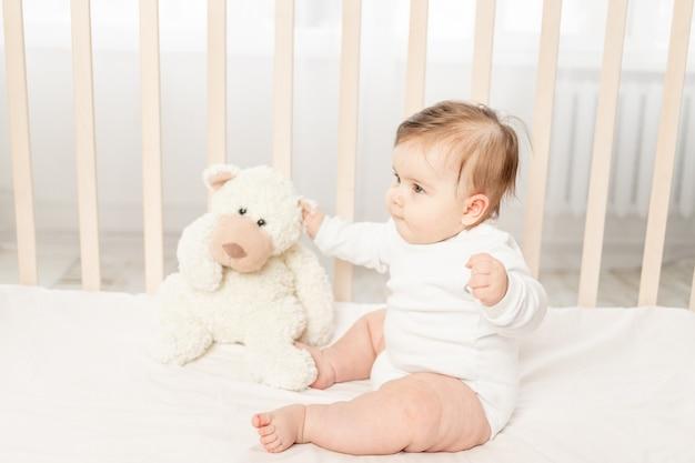 Baby zes maanden spelen in een wieg in een wit rompertje met een teddybeer Premium Foto
