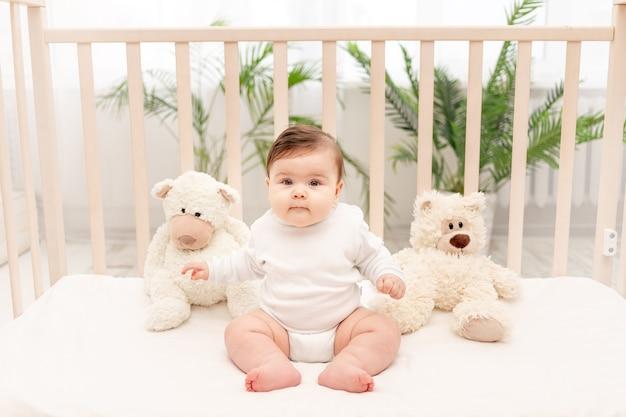 Baby zes maanden zittend in een wieg in een wit romper met speelgoed teddyberen Premium Foto