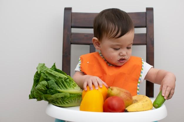 Zitstoel Voor Baby.Baby Zit Op De Stoel En Plukt De Groente Om Te Eten Foto Premium