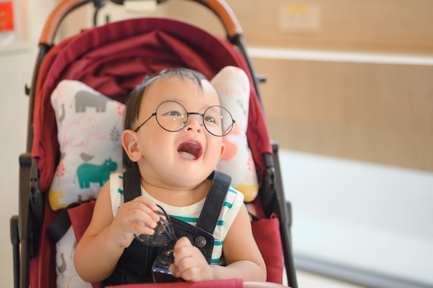 Babyjongen die glazen draagt die in moderne wandelwagen zitten. reizen met jonge kinderen. vervoer voor gezin met baby. Premium Foto