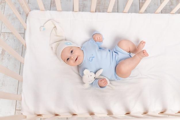 Babyjongen in wieg met teddybeer speelgoed gaat naar bed of werd wakker in de ochtend, familie en geboorte concept Premium Foto