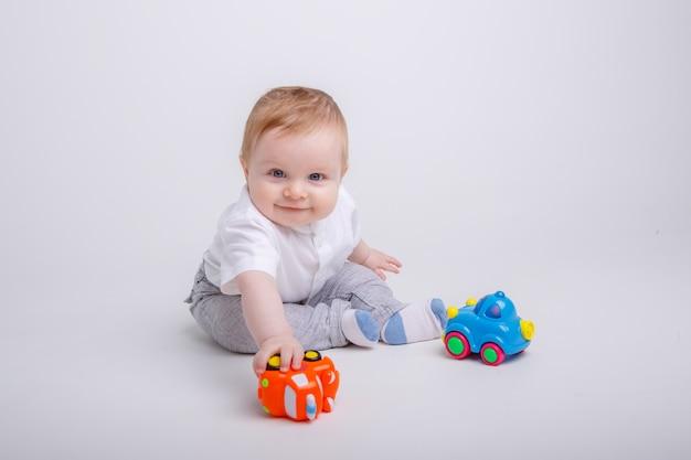 Babyjongen spelen met speelgoedauto's op witte achtergrond Premium Foto