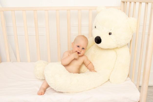 Babyjongen zit in luiers in een wieg met een teddybeer Premium Foto