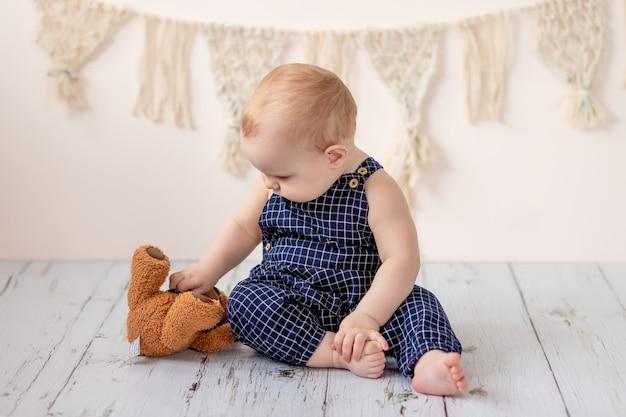 Babyjongen zittend met een teddybeer speelgoed op de vloer Premium Foto