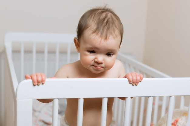 Babymeisje in een luier die in de wieg spelen. zeer grappige gezichtsuitdrukking. Premium Foto
