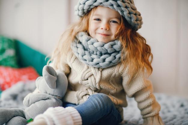 Babymeisje in gebreide muts en sjaal Gratis Foto
