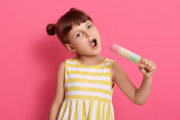 Babymeisje kind houdt groot ijs als microfoon en zingt, vrouwelijk kind stelt zich voor dat ze zangeres en zingt met waterijs in handen op roze muur. Gratis Foto