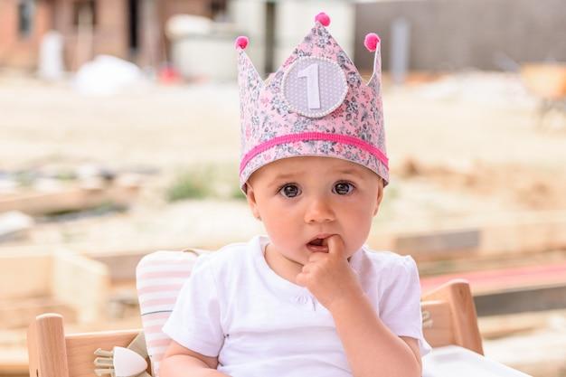 Babymeisje met een roze kroon op haar eerste verjaardag Premium Foto