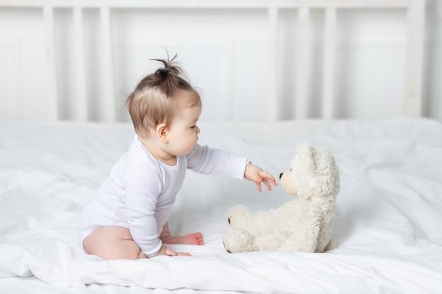 Babymeisje spelen met een teddybeer speelgoed op het bed thuis, het concept van spelen en ontwikkeling van kinderen Premium Foto